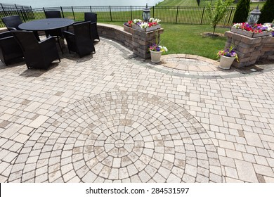 Ornamental brick paved outdoor patio with a circular design in the bricks with dining furniture and colorful flowers in flowerpots flanking steps and an entrance, view from above after rain