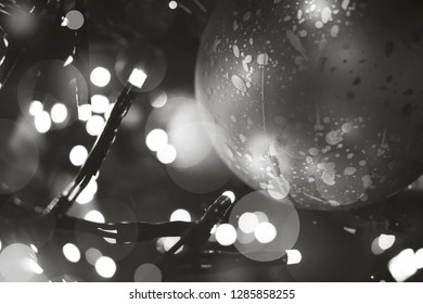 Ornamental christmas ball hanging in a christmas tree with lights from close-up
