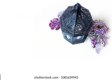 Ornamental dark Moroccan, Arab lantern with lilac flowers on the white table. Greeting card for Muslim holy month Ramadan Kareem. Festive background. Empty space. Flat lay, top view.