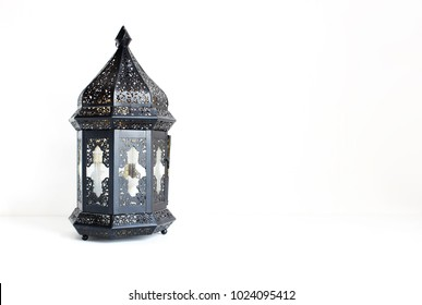 Ornamental dark Moroccan, Arabic lantern on the white table. Greeting card for Muslim community holy month Ramadan Kareem. Festive background with a lot of empty space.