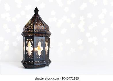 Ornamental dark Moroccan, Arabic lantern on the white table. Burning candle, glittering bokeh lights stars. Greeting card for Muslim community holy month Ramadan Kareem. Festive background.