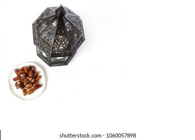Ornamental dark Moroccan, Arabic lantern and plate with date fruits on the white table. Greeting card for Muslim holy month Ramadan Kareem. Festive background. Empty space. Flat lay, top view.