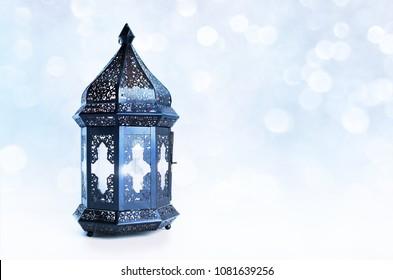 Ornamental dark Moroccan, Arabic lantern on the table. Burning candle, glittering bokeh lights stars. Greeting card for Muslim community holy month Ramadan Kareem. Festive blue blurred background.