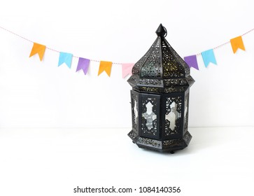 Ornamental dark Moroccan, Arabic lantern on the white table. Party decoration, string of colorful paper flags. Greeting card for Muslim holiday Ramadan Kareem. Festive background.
