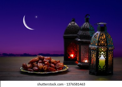 Ornamental dark Moroccan, Arabic lantern and dates on on an old wooden table with the night sky and the Crescent moon and the star behind. Greeting card for Muslim community holy month Ramadan Kareem.