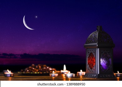 Ornamental dark Moroccan, Arabic lantern and dates on on an old wooden table with the night sky and the Crescent moon and the stars behind. Greeting card for Muslim community holy month Ramadan Kareem