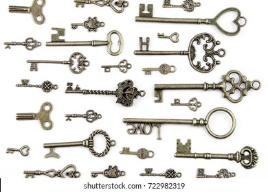 Ornamental medieval vintage keys with intricate forging, composed of fleur-de-lis elements, victorian leaf scrolls and heart shaped swirls. antique golden door key isolated on white background