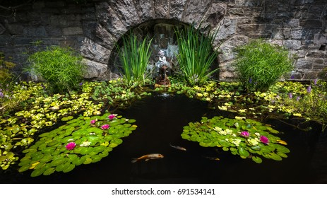 Ornamental pond with assorted aquatic plants, stone wall, and masonry fountain