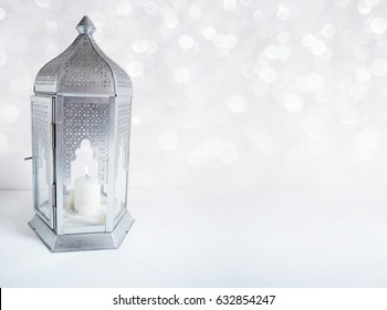 Ornamental silver Arabic lantern on the table with glittering bokeh lights. Greeting card for Muslim community holy month Ramadan Kareem. Festive blurred background with a lot of empty space.