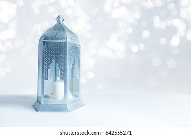 Ornamental silver and blue Arabic lantern on the table with glittering bokeh lights. Greeting card for Muslim community holy month Ramadan Kareem. Festive blurred background with a lot of empty space.