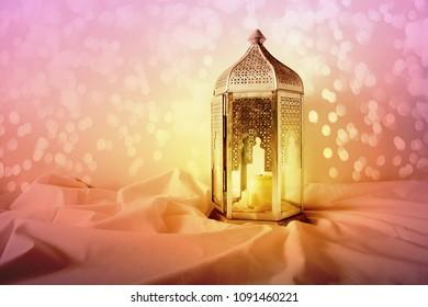 Ornamental silver Moroccan, Arabic lantern on linen throw. Burning candle, glittering colorful bokeh lights. Greeting card for Muslim community holy month Ramadan Kareem. Festive background.