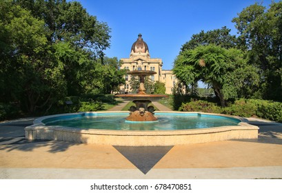 Ornamental stone fountain and reflecting pool with the Saskatchewan Provincial Legislative Building in the background located in Wascana Park in Regina, Canada