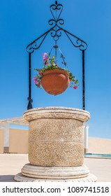 ornamental stone patio well and hanging terra cotta flower basket with geraniums against a blue sky