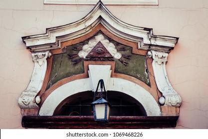 Ornamentation above a building entrance with illuminati symbolic. Recorded in Poland.