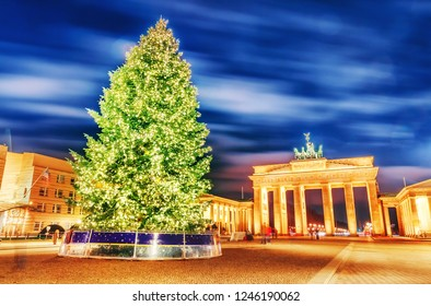 Ornamented and illuminated green Christmas tree on Brandenburg Gate international landmark site in Berlin, the capital of Germany, Europe. Symbol of Christmas and New Year. Winter scene, December.