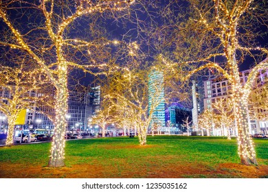 Ornamented illuminated trees on Potsdamer Platz in Berlin, Germany. Christmas time in Berlin. December winter holidays background.