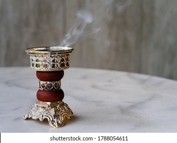 Ornate Arabian Bakhoor incense burner censer emitting white smoke. With copy space