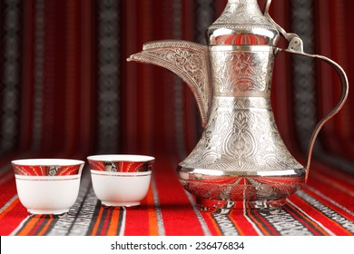 Ornate arabian tea cups and a dallah are placed on traditional red fabric from the gulf region.