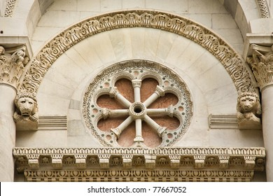 An ornate arch and circular stone carving over the door of the cathedral in Lucca, Italy