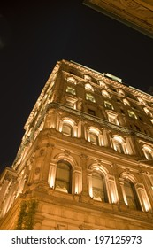 An ornate building with many windows illuminated in the evening.