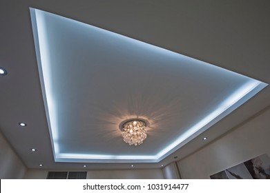Ornate chandelier style ceiling light inside luxury apartment with LED lighting surround