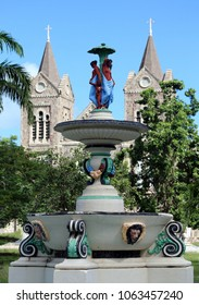 ornate and colorful fountain in park with church steeples in background, Basseterre, St. Kitts, Lesser Antilles, Caribbean