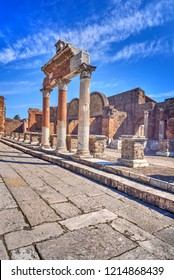Ornate columns in the ruins of ancient Pompeii near Naples, Italy. Ancient paving stones are featured in the forground of this deep perspective image.