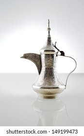 An ornate dallah which is a metal pot with a long spout designed specifically for making Arabic coffee