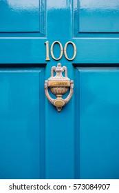 Ornate door knocker on dark cyan door in the UK.