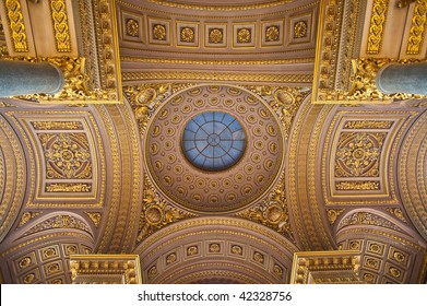 Ornate gilded gold ceiling details at the palace of Versailles. Fancy filigree and marble columns adorn the overhead arches.