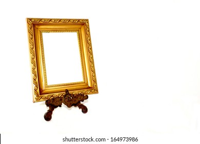 ornate gold picture frame on vintage metal stand