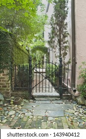 The ornate iron Gate and side entrance to an eighteenth century private garden and residence in a cobblestone and brick paved alley in Charleston, South Carolina.