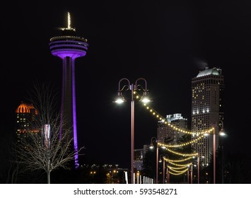 Ornate lamp post with golden lit walkway leading to city with tower, vibrant night travel tourism scene
