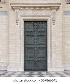 A ornate moldings above a large green entrance door to the Pantheon in Paris France.