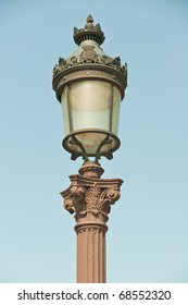 An ornate, old-fashioned streetlight in Paris.