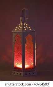 An ornate red glass lantern with a candle  burning inside