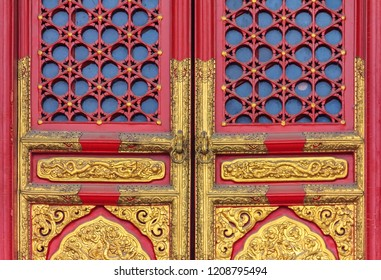 Ornate red wooden door with gold trim and traditional Chinese design at the Forbidden City, In Beijing, China