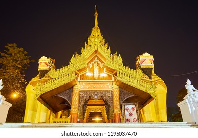 The ornate South Gate of Shwedagon Zedi Daw with statues of leogryphs (chinthe), wooden lattice, carved gilt decors of pyatthat roof, Yangon, Myanmar.