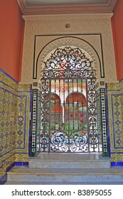 Ornate tile work in the gated entrance to a private Spanish courtyard garden in Seville.