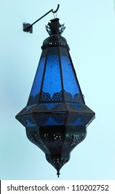 Ornate traditional blue moroccan lamp hanging from a stucco wall