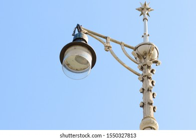 Ornate vintage white painted wrought iron lamp post viewed from below against a clear blue sky with copy space