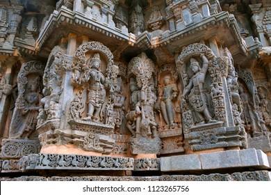 Ornate wall panel reliefs depicting from left Goddess Lakshmi, deities, a sage, and Krishna as Govardhan Giridhari, Kedareshwara temple, Halebidu, Karnataka