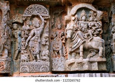 Ornate wall panel reliefs depicting From left Krishna as Govardhan Giridhari and Shiva-Parvati seated on Nandi, Kedareshwara temple, Halebidu, Karnataka