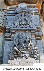 Ornate wall panel reliefs depicting Lord Vishnu with his consort Lakshmi sitting in his lap, Chennakesava temple, Belur, Karnataka.