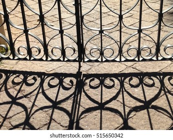 Ornate wrought iron fence throwing a shadow