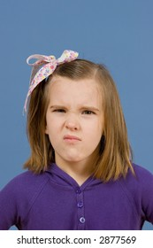 Ornery little girl with a ribbon in her hair and a grumpy expression on her face on a blue background.