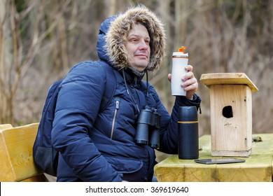 Ornithologist drinking tea in park near wooden bird cage