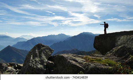 OROBIE MOUNTAINS, ITALY - CIRCA AUGUST 2017:  a hiker stands on a big boulder in the Orobie mountains and admires the beauty of  nature.
