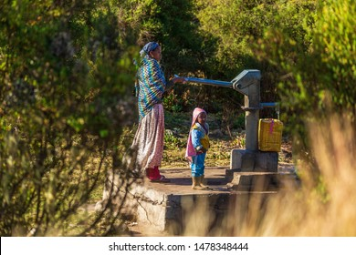 OROMIA, ETHIOPIA-JAN 21, 2019: Unidentified mother with child pumping water from a source.