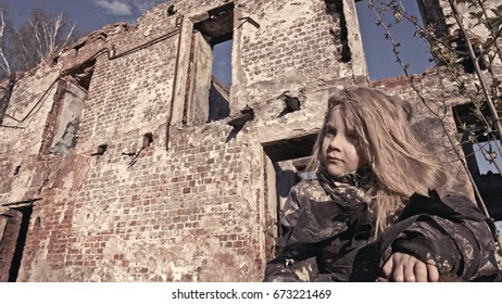 The orphaned child of the homeless cries about the ruins. Terrorism, war. Young girl covered in mud.